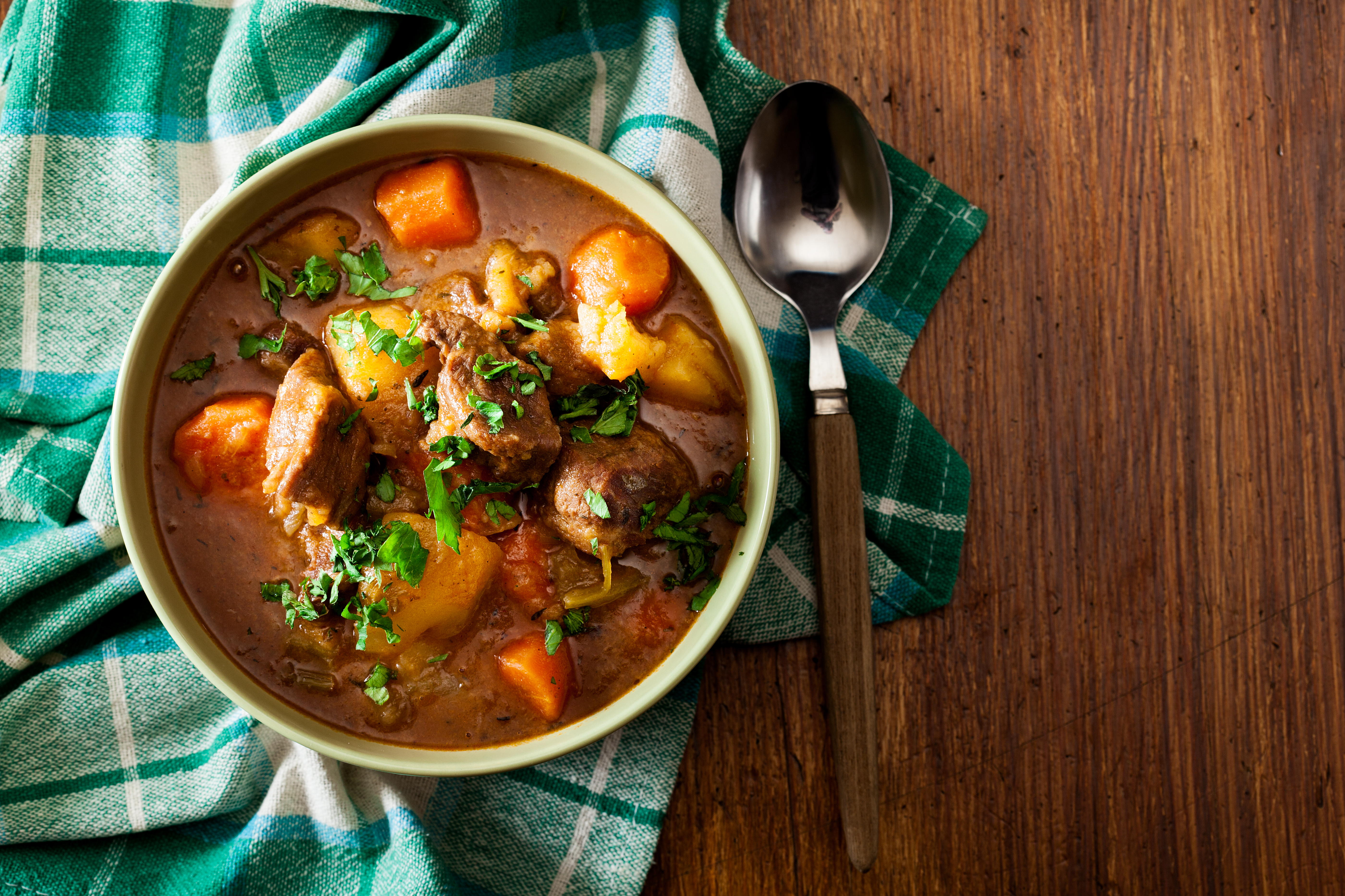 bowl of irish stew on a wooden table