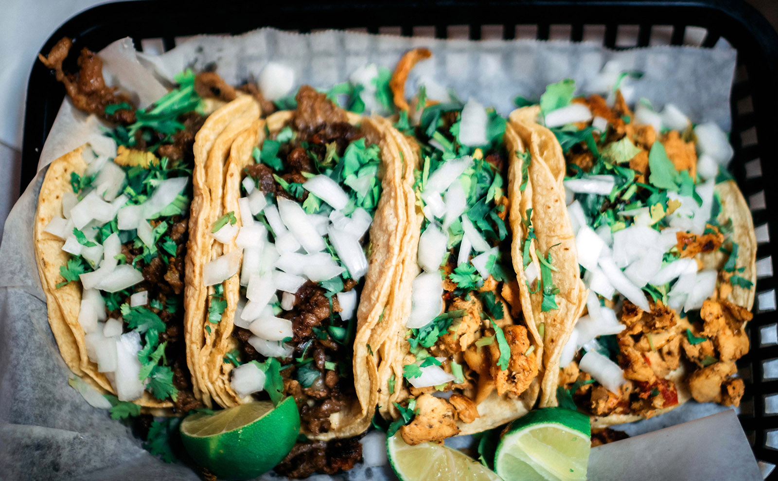 platter of soft tacos with onion and cilantro