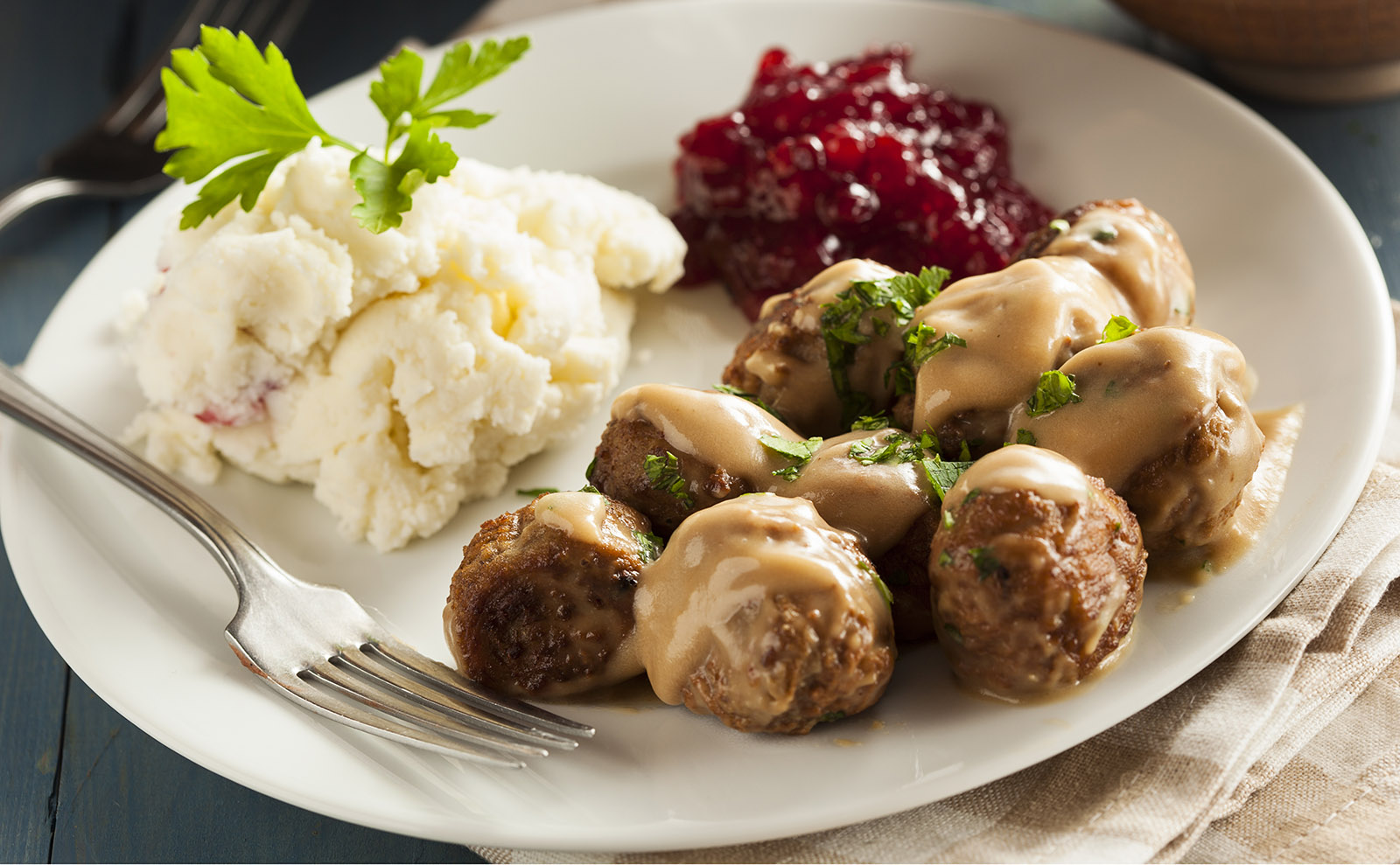 swedish meatballs in gravy with mashed potatoes and lingonberry jam