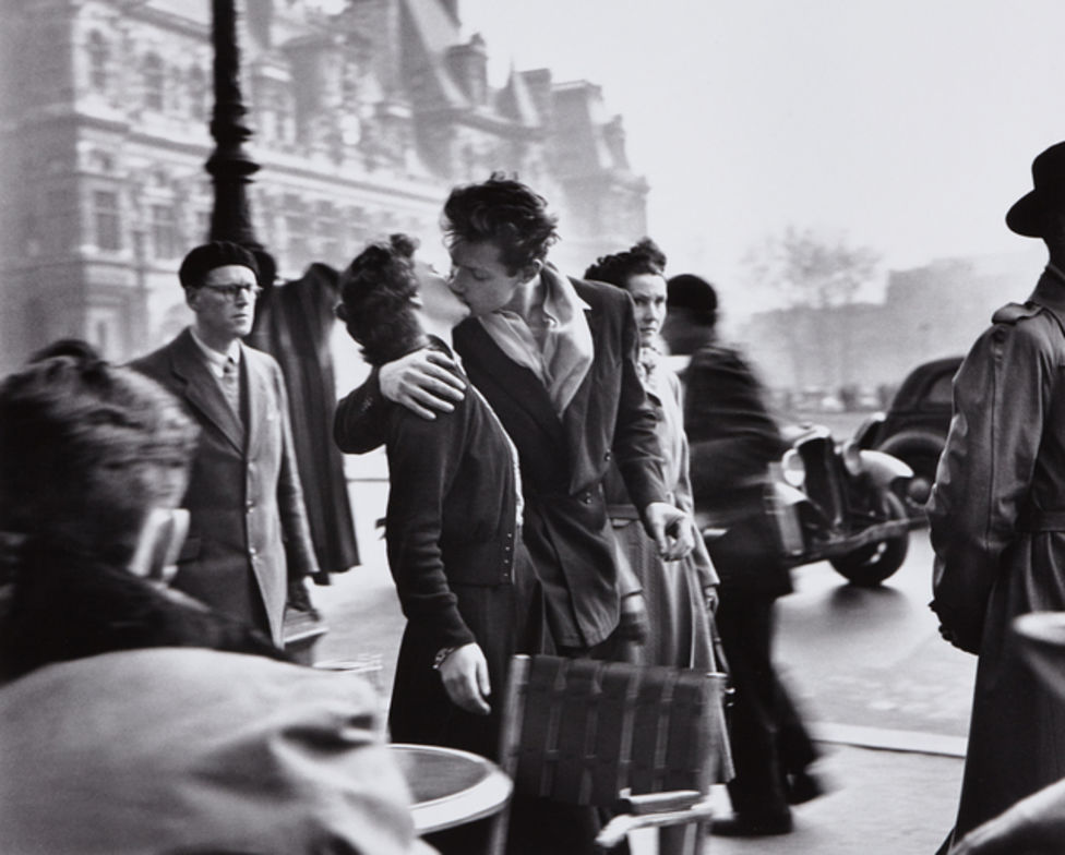 black and white photo of a man and woman kissing in paris