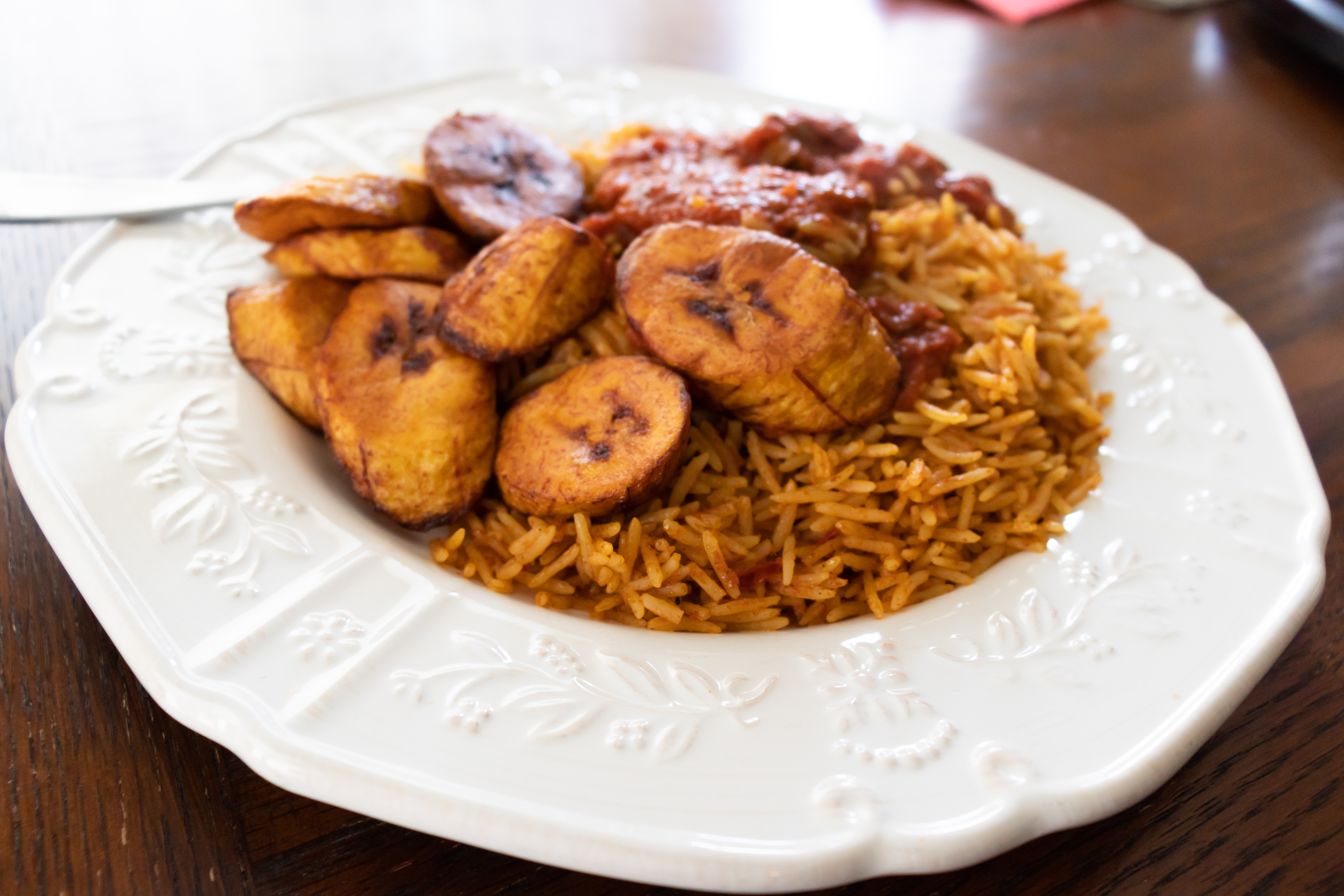 white bowl of jollof rice with fried plantains