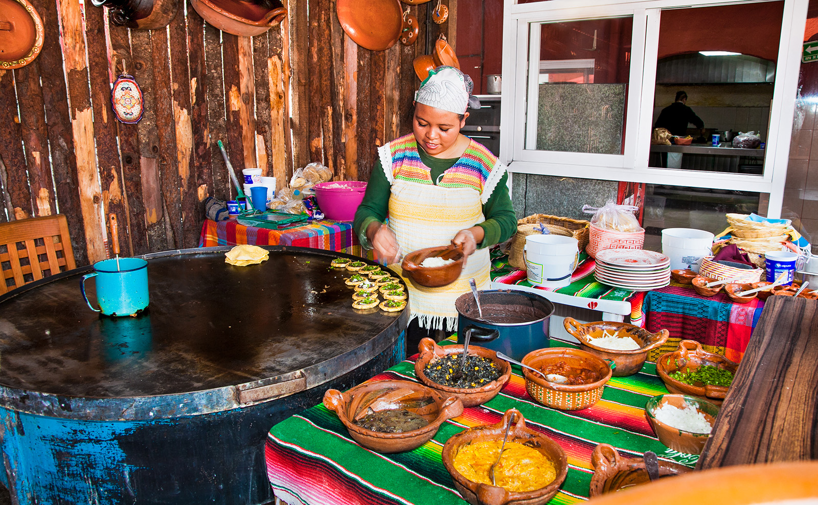 mexican girl cooking food surrounded by colorful bowls in Teotihuacan, Mexico