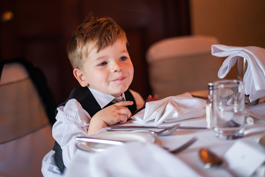 Sweet page boy watching wedding guests at Dalhousie Castle wedding reception