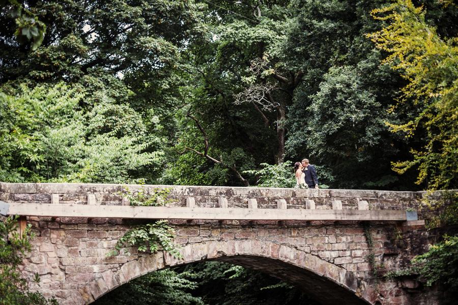 Bride and groom kissing on the bridge at Dalhousie Castle in Bonnyrig
