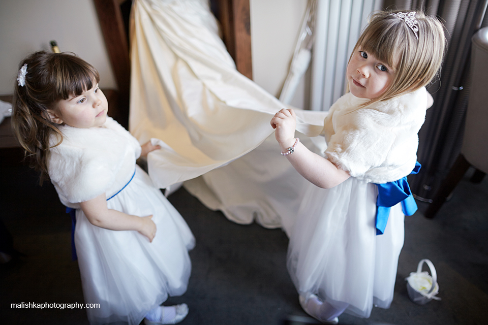 Little bridesmaids helping the bride with her dress