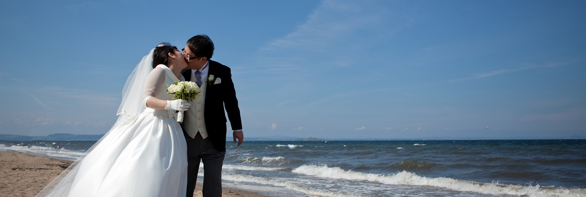 Bride and groom kissing on Portobello beach