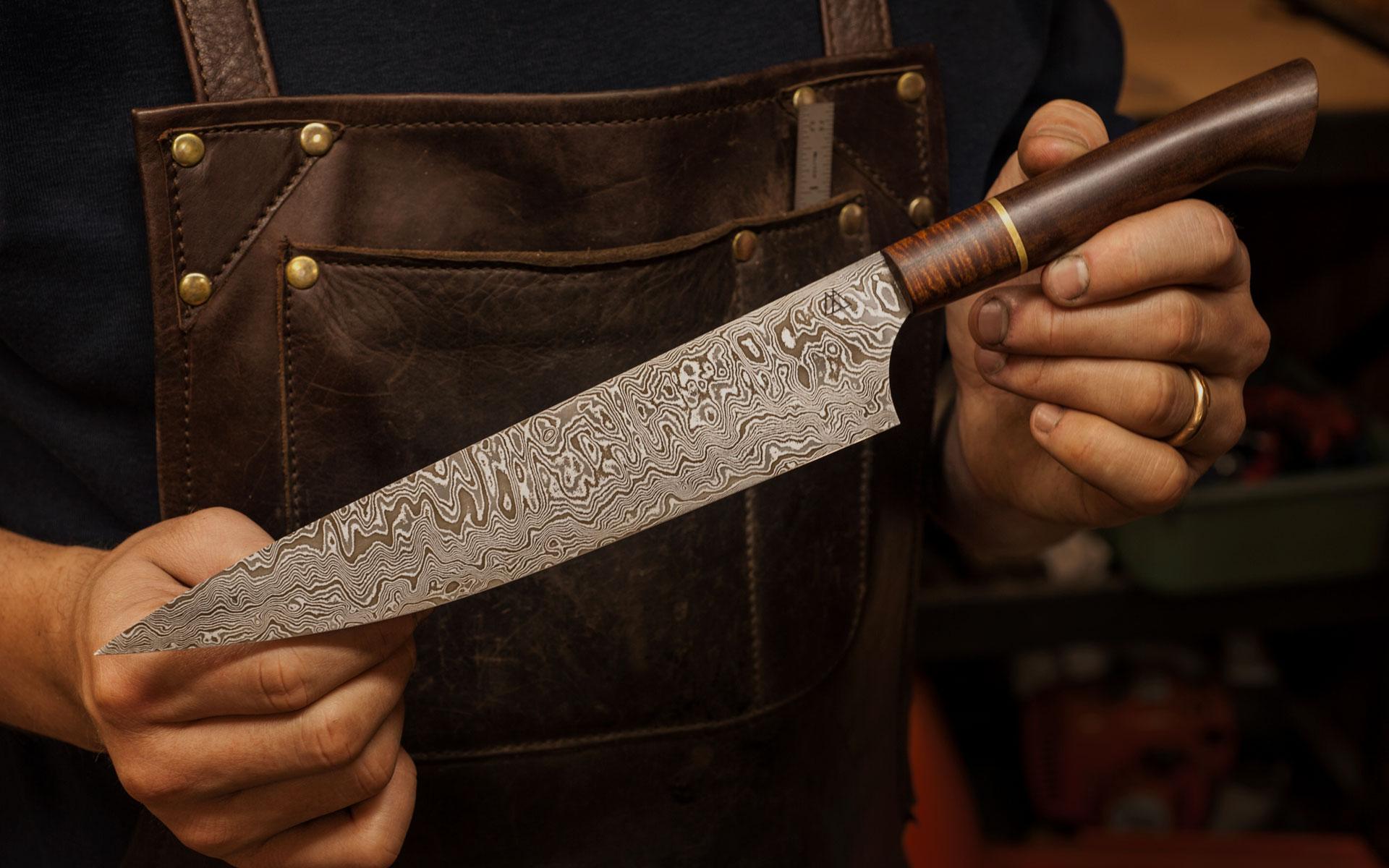 Mathieu holding knife wearing brown apron.