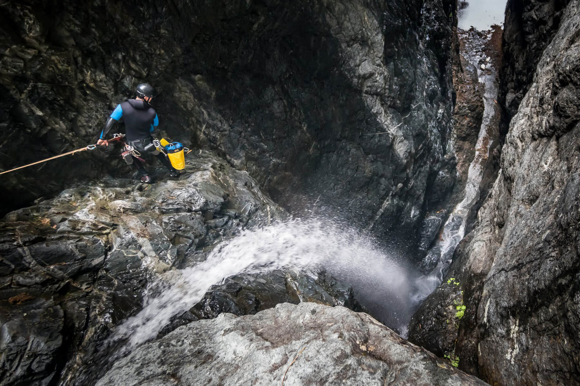 Pete Choate taking a look over the edge in Tesseract, a deep, low flow canyon off the Middle Fork Snoqualmie River, Washington, first descent 2018. Photo by Kevin Steffa.