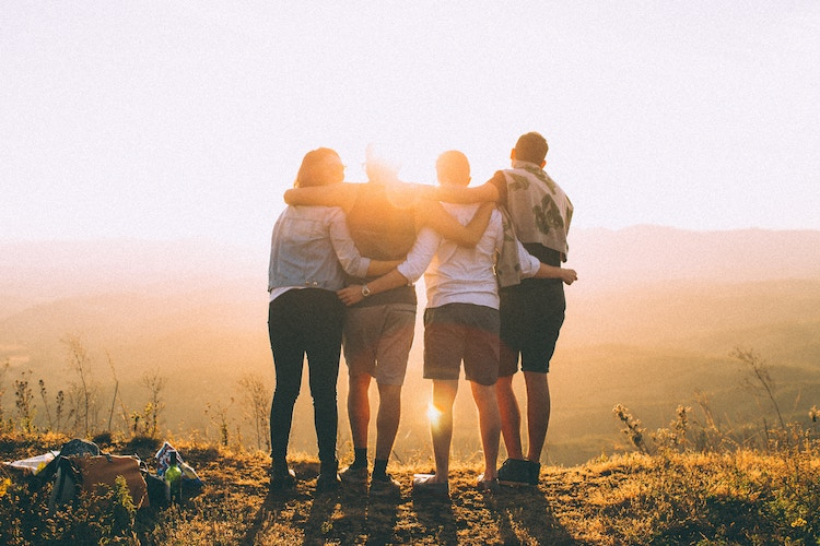 Four people huddling together looking to the sunset.