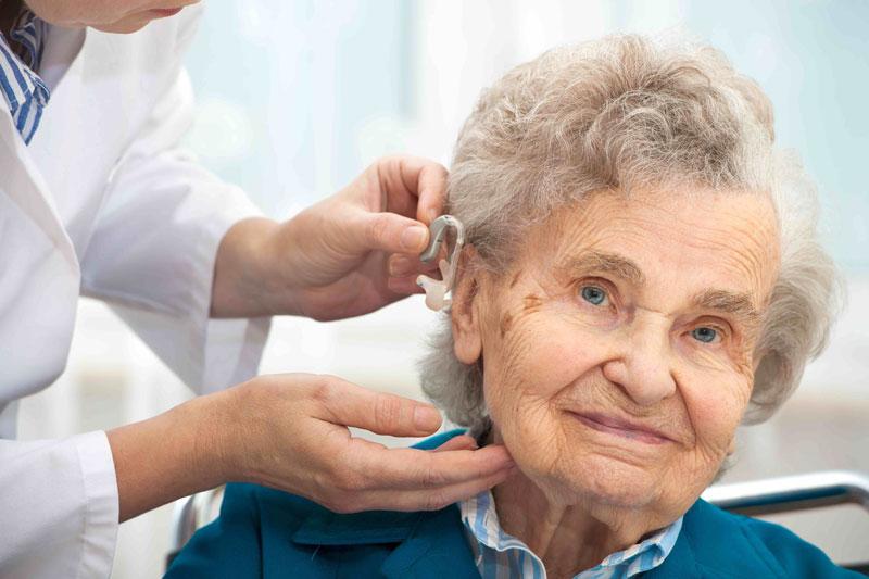 elderly women having hearing aid put on