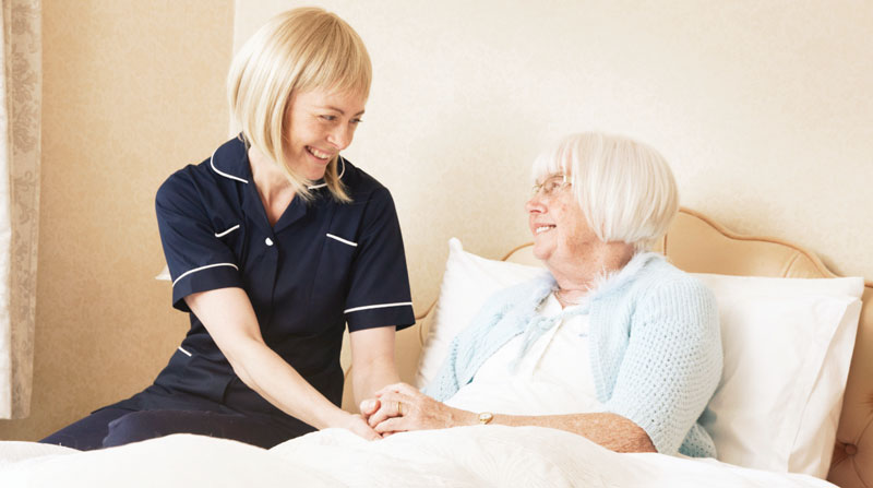 caregiver sitting on a bed with a senior woman who needs home care