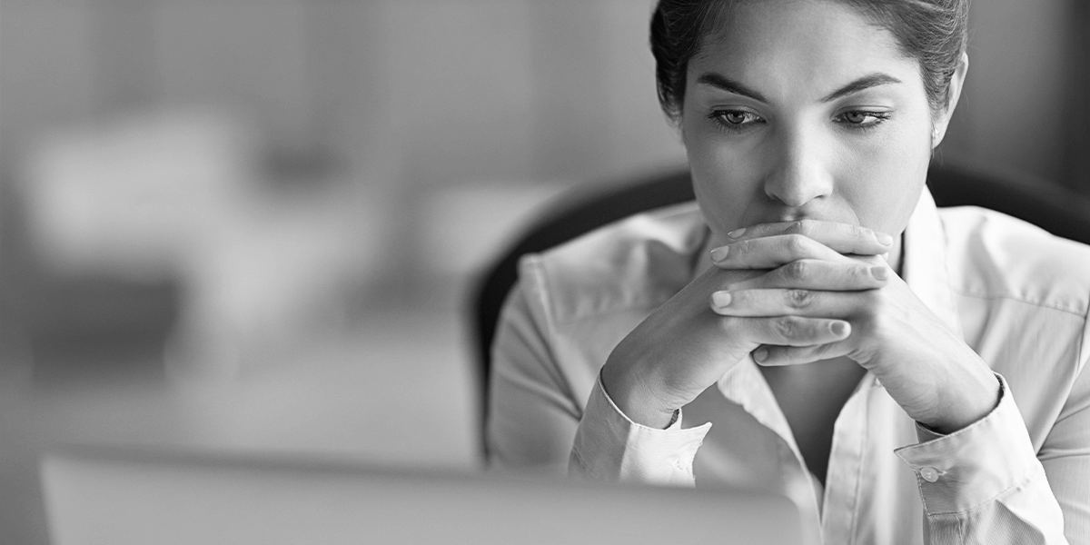 A woman sits at her desk, resting her head on her hands, deep in thought.