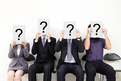 A group of seated business people with a large question mark covering their heads