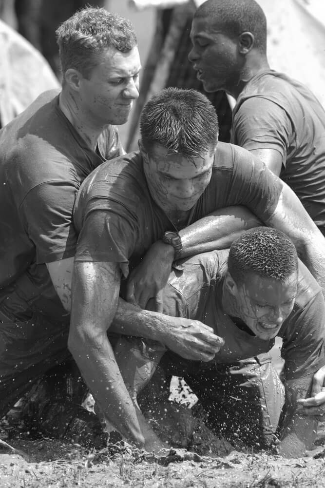Group of men covered in mud struggling to cooperate.