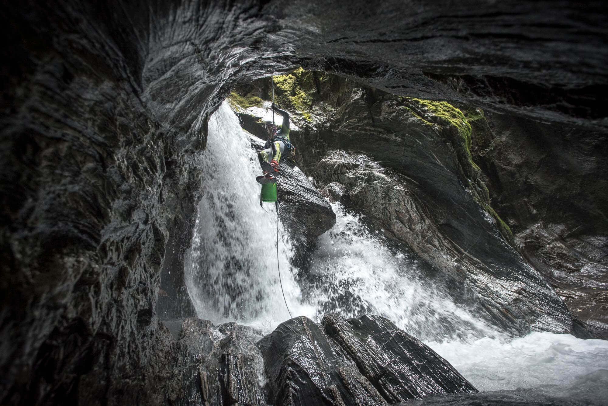 International canyoning training programs by V7 Academy allow you to learn canyoning online. Complete canyoning training courses from beginner to advanced. Pictured here is a person rappelling down a waterfall in a canyon in New Zealand; the person is hanging on a rope using a Seland wetsuit and Adidas Hydrolace shoes, and uses a canyoning descender to rappel down safely.