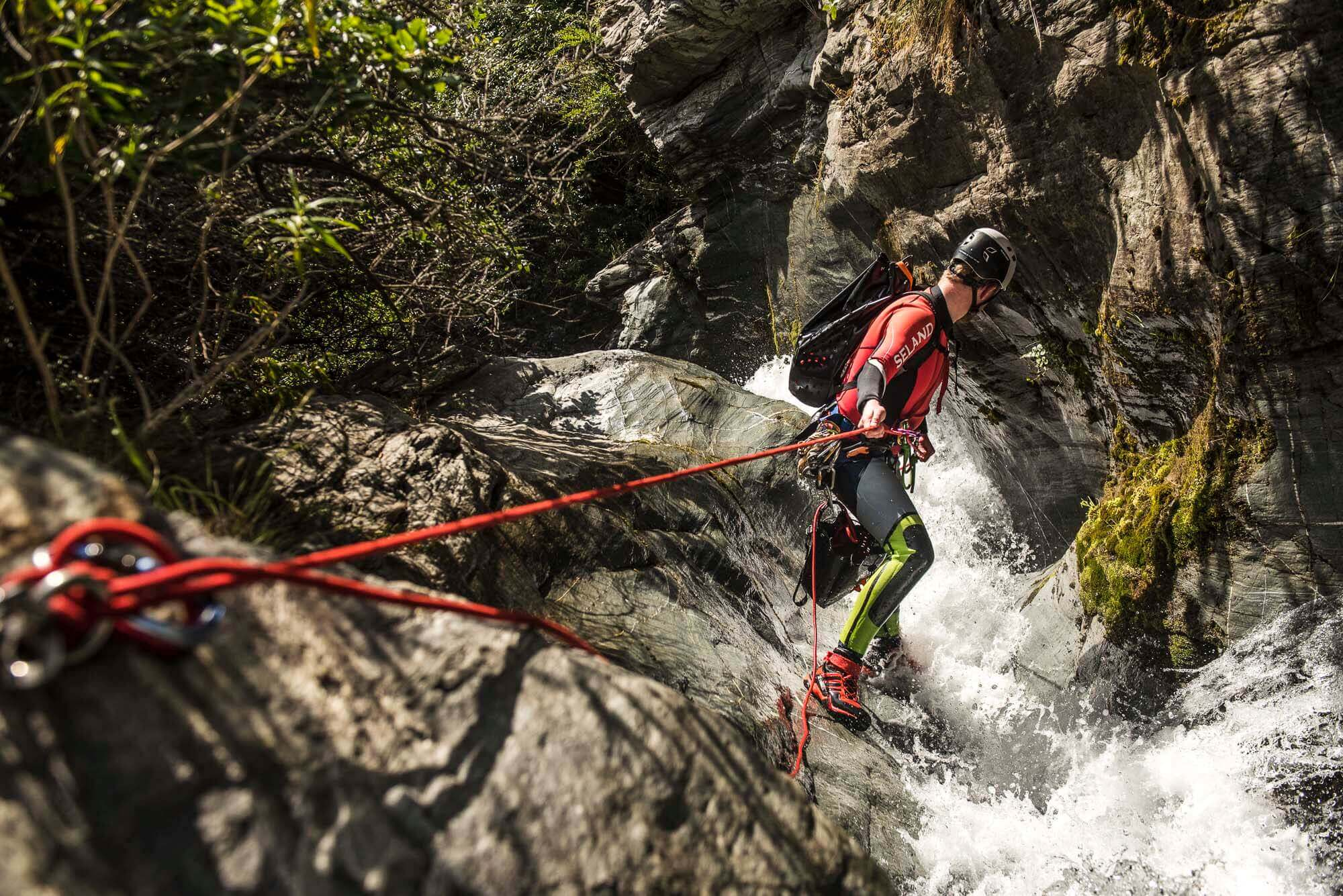 Online Canyoning Courses with V7 Academy are the best way to learn canyoning. Canyoning certifications with V7 Academy. Picture shows a canyoneer rappeling while using a red rope and a red top. Image by Gus Schiavon (@v7gus)
