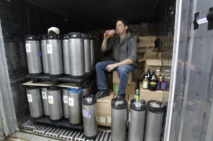 In this photo made July 1, 2010, Will Savitri, owner of Katalyst Kombucha fermented tea, takes a drink of tea from inside his refrigerated storage unit at the Katalyst Kombucha company in Greenfield, Mass. Regulators and retailers are concerned that the ancient and trendy tea may need to be regulated as an alcoholic drink. That's because some bottles have more than 0.5 percent alcohol, the legal limit for a drink not to be considered alcoholic. (AP Photo/Charles Krupa)