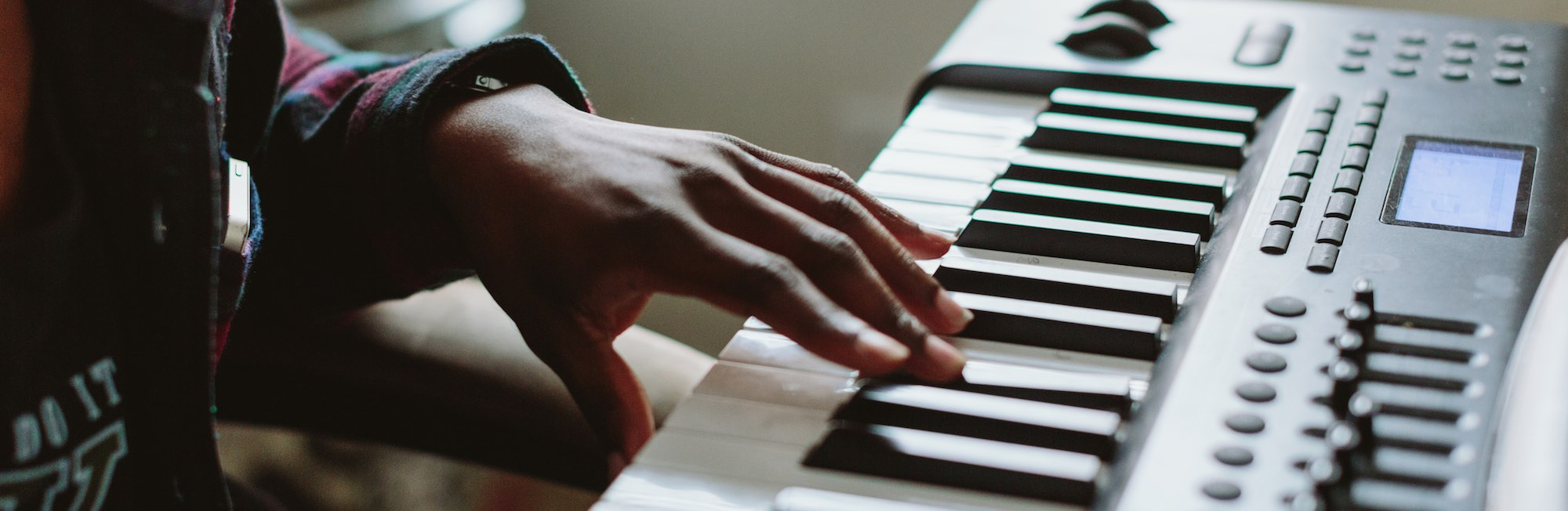 A photo of a left hand playing an F sharp with middle finger on an electric piano keyboard