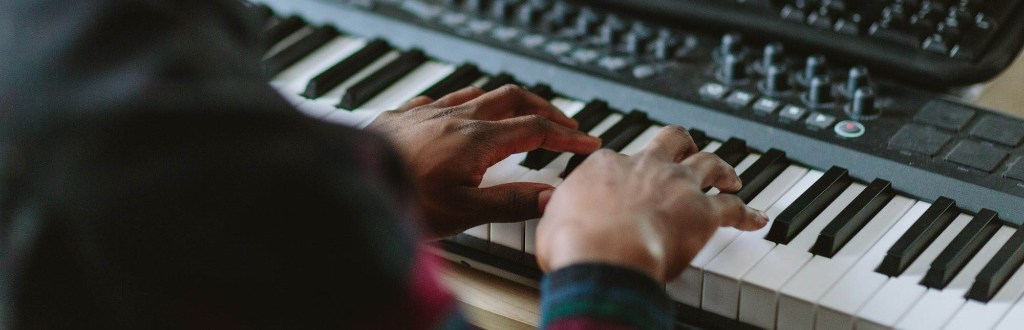 A photo of the arms and hands of a young person in a plaid shirt with both hands resting on the keys of a synthesizer keyboard that features many manual control dials