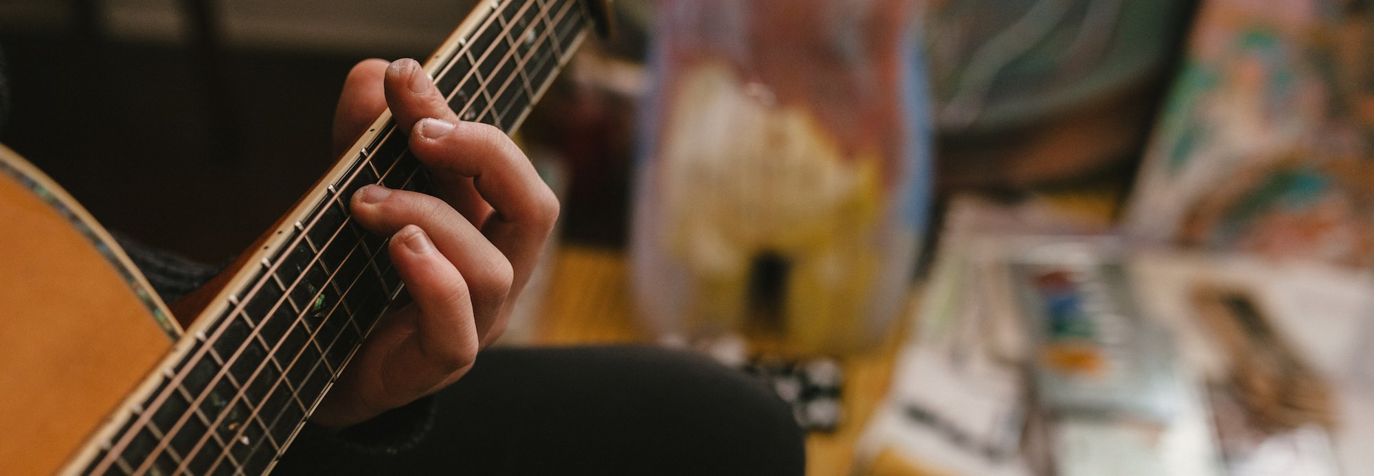 A photo of a hand on the fingerboard of a steel-stringed acoustic guitar, with a blurred background scene of objects in the room. The fingernails on the hand have been bitten very short.
