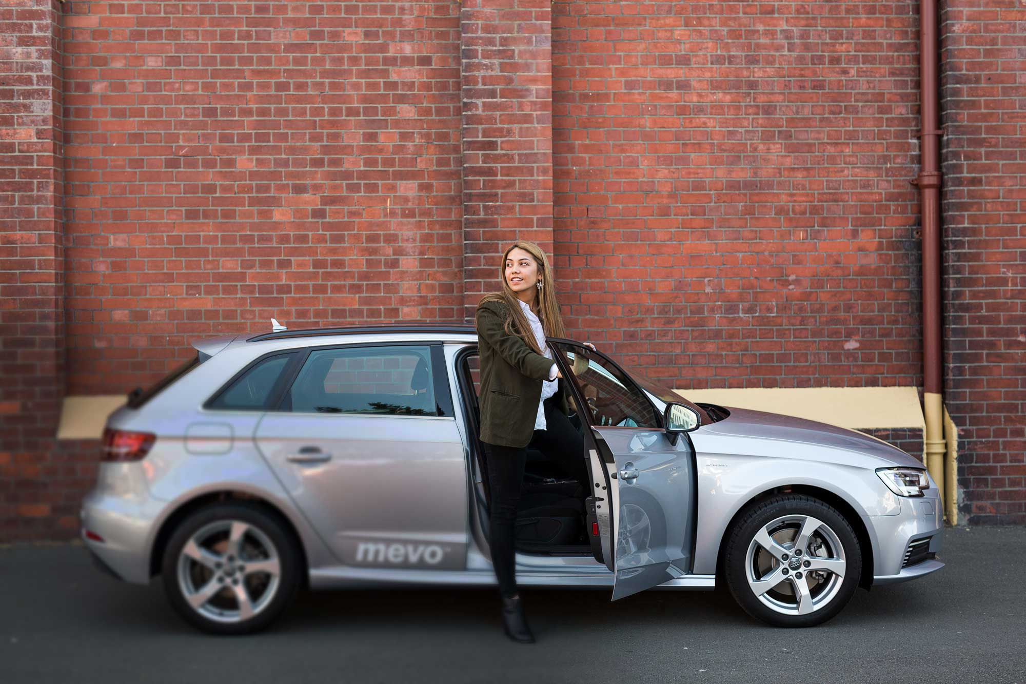 Woman getting out of Audi A3 e-tron in the city