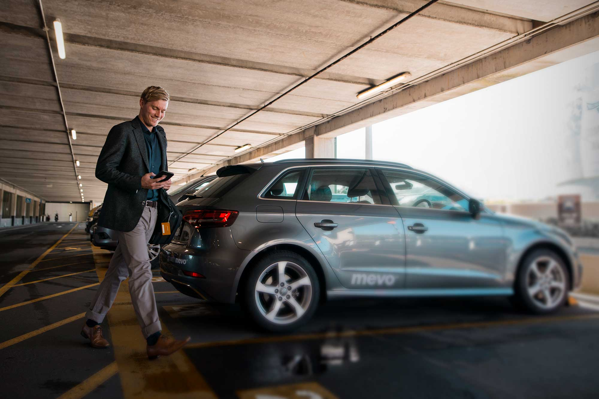 Man opening Audi A3 e-tron with his smartphone at Wellington Airport