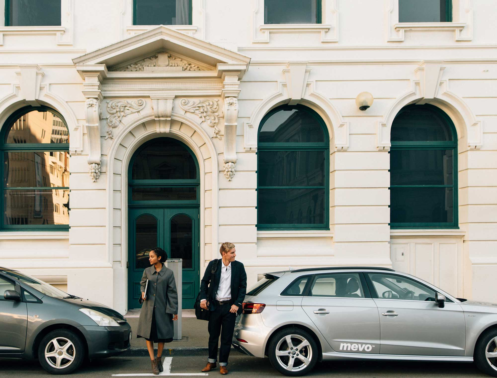 Man and woman next to Mevo Audi A3 e-tron on a city street