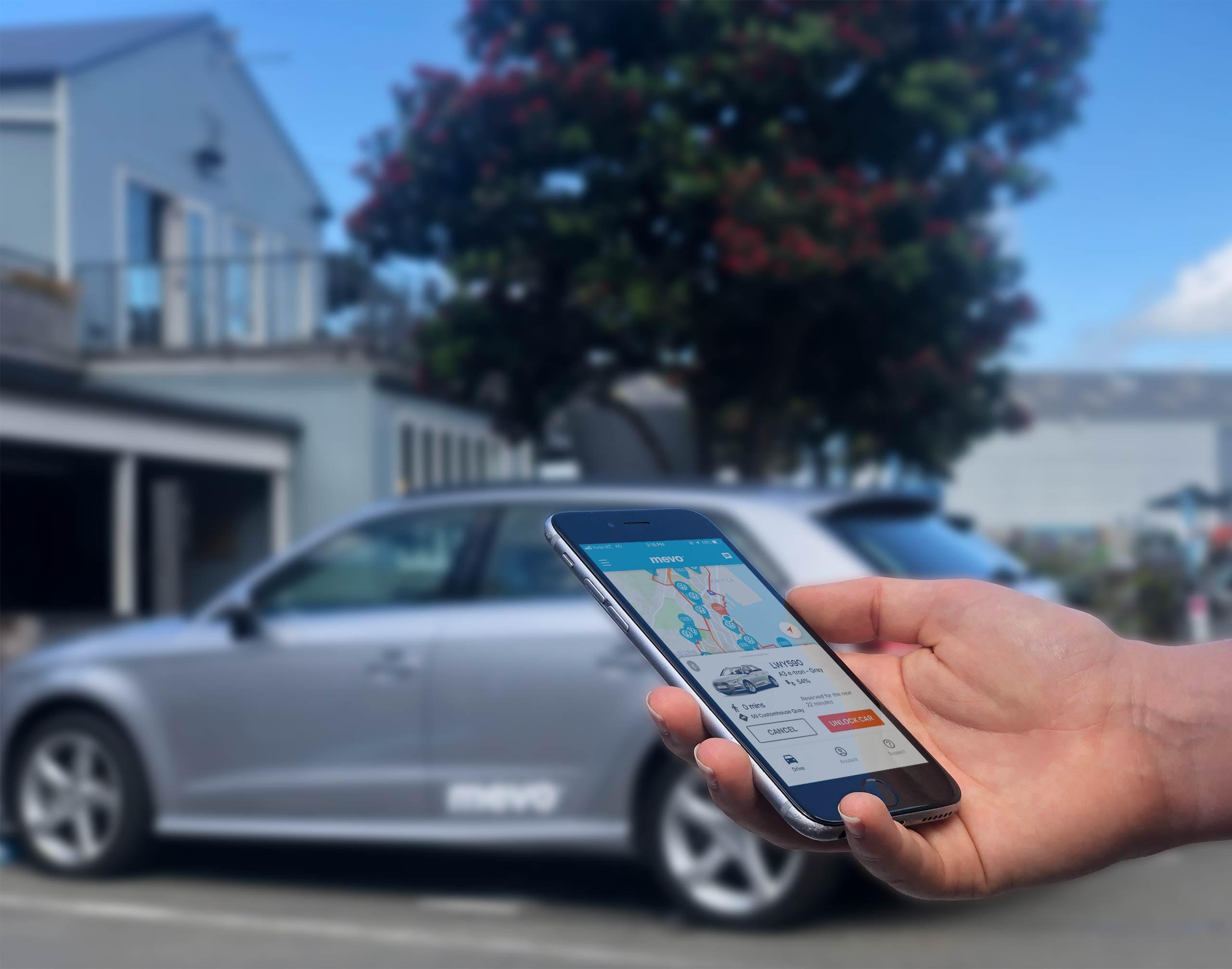 Mevo app on an iPhone being held in front of a Mevo car