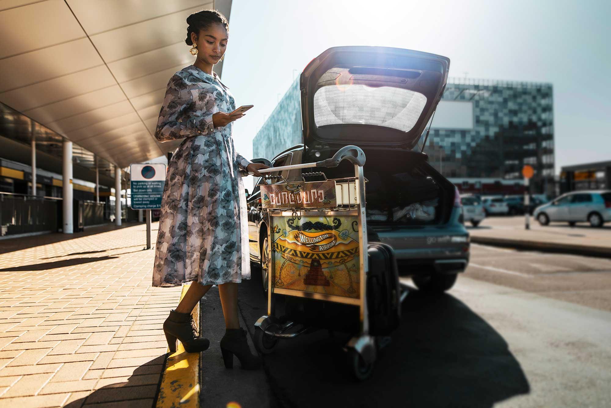 Woman at Wellington airport loading her bags into a Mevo Audi A3 e-tron
