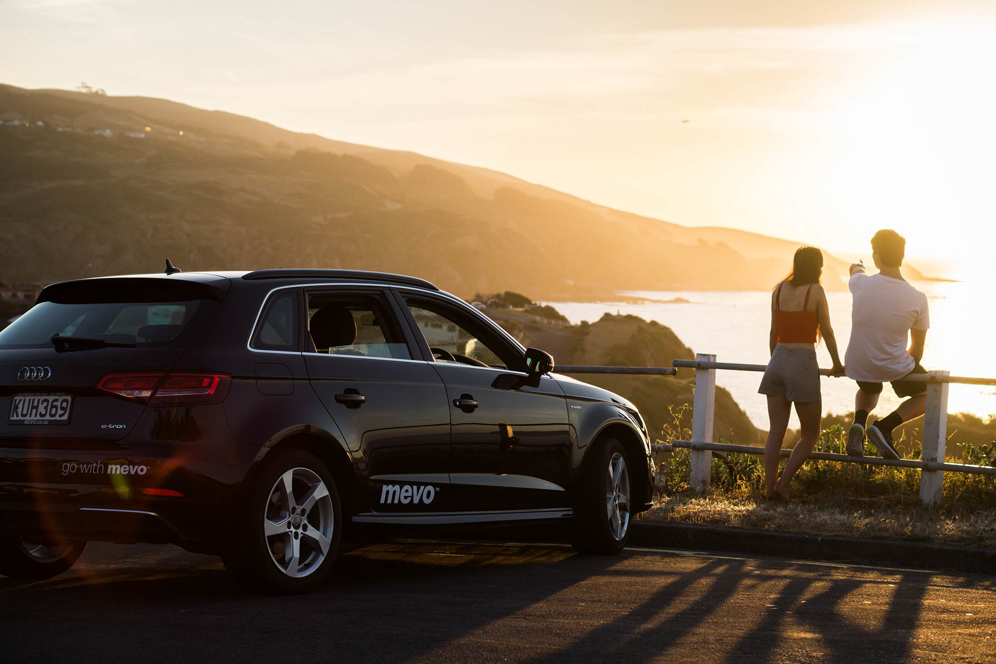 Young couple sitting on a fence next to a Mevo Electric Car